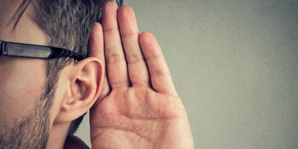 man met zwarte bril actief aan het luisteren, met focus op het oor