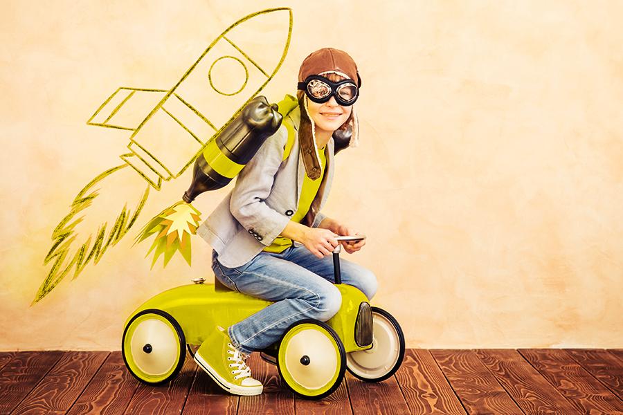 meisje op speelgoed tractor voor egale muur met raket erop getekend, ze draagt een pilotenbril en muts, flessen op de rug stellen raket voor, enthousiast, klaar om te vertrekken