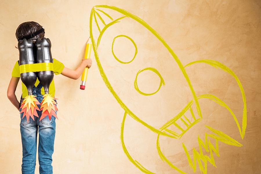 meisje met flesraketten op de rug staat voor egale muur en tekent er raket op met geel potlood, als metafoor voor interesse in job