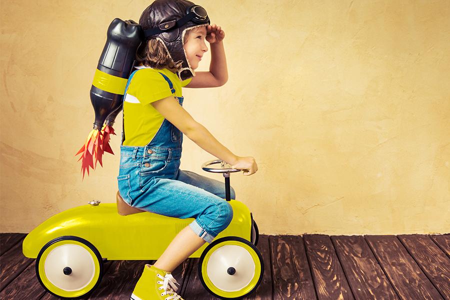 meisje op speelgoed tractor voor egale muur, ze draagt een pilotenbril en muts, flessen op de rug stellen raket voor, houdt hand tegen voorhoofd, kijkt naar de toekomst, klaar voor top job, lacht