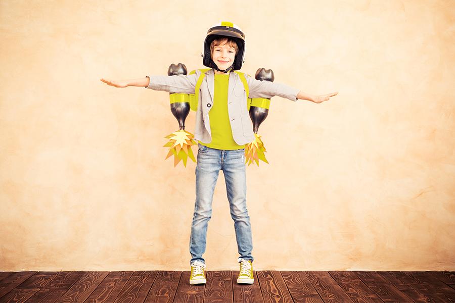 meisje met helm en 2 flesraketten op de rug staat voor egale muur met armen gespreid, doet vliegtuig na, lacht