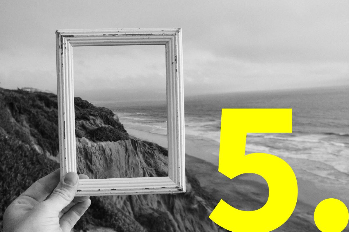 Hand houdt fotokader vast waardoor je kan kijken naar het landschap met zee en bergen.