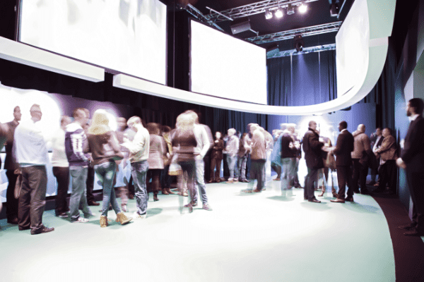 Beursopening met veel bezoekers en grote schermen aan de muur.