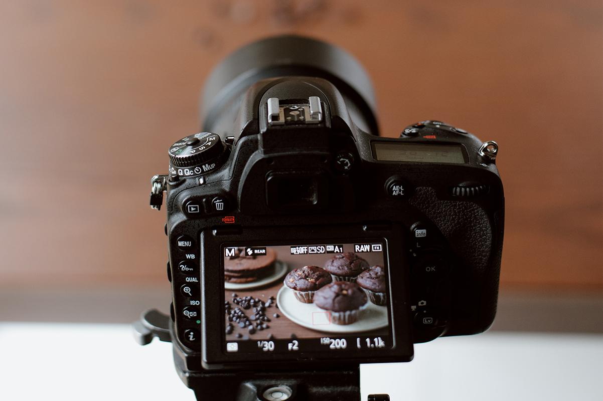 Close-up van fototoestel tijdens shoot van chocolade cupcakes en pannenkoeken.