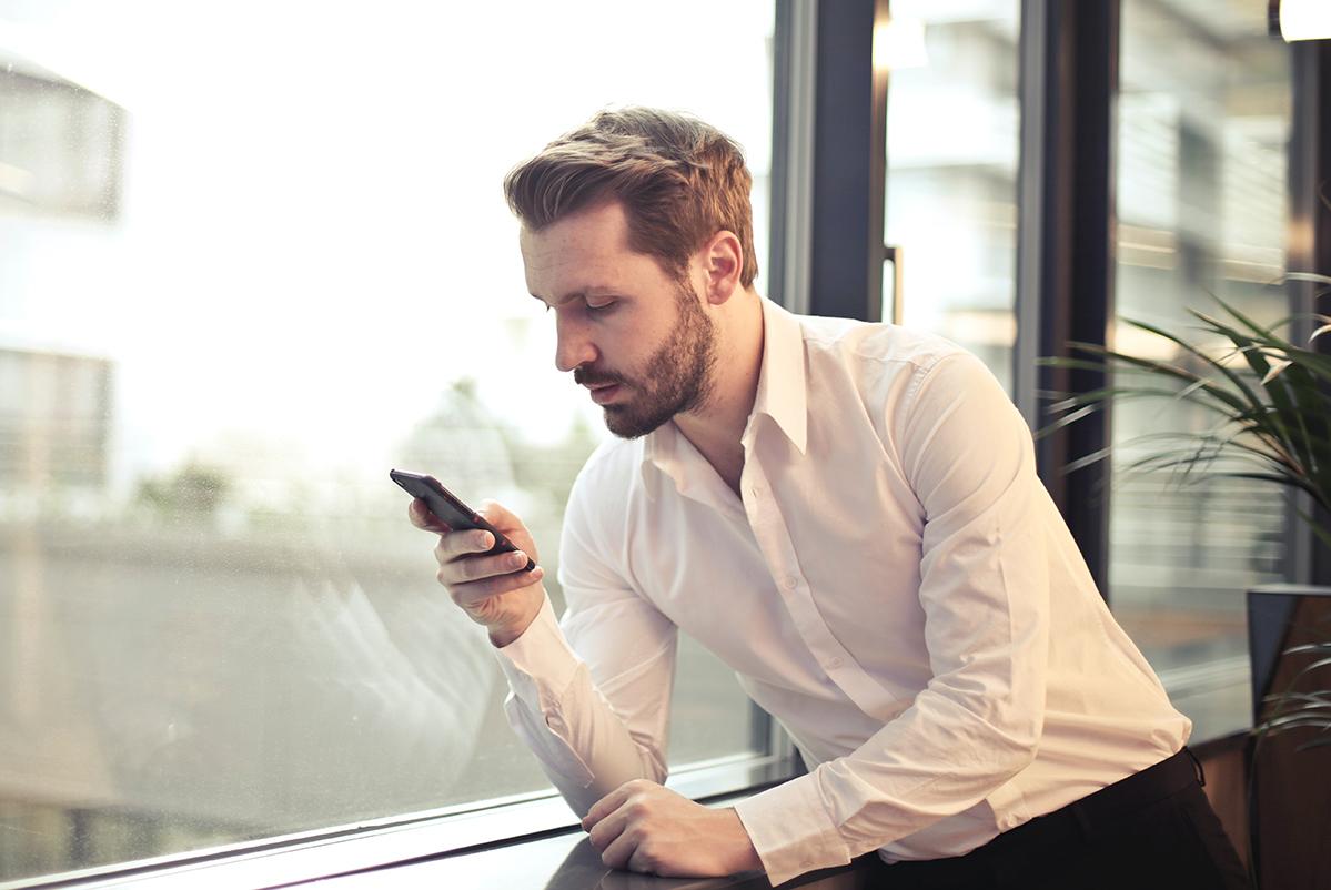 Jonge zakenman staat aan raam in kantoor en bekijkt promotievideo op smartphone.