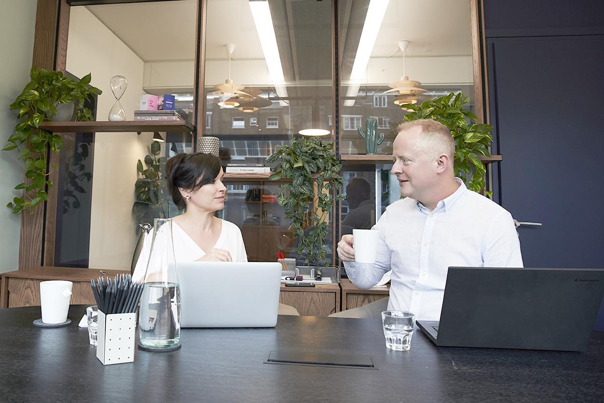 Zakenman en vrouw zitten in vergaderzaal en drinken koffie tijdens de verkooppresentatie.