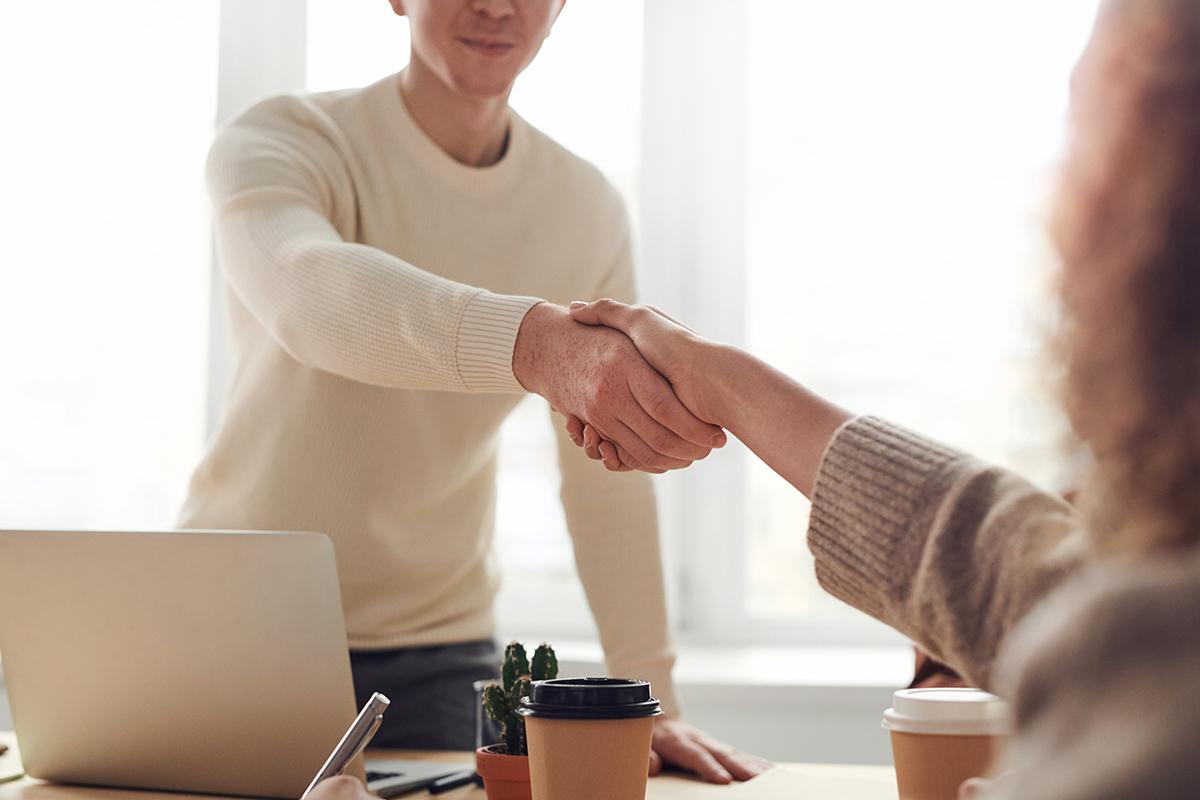 Zakenmensen schudden handen op geslaagde overeenkomst.