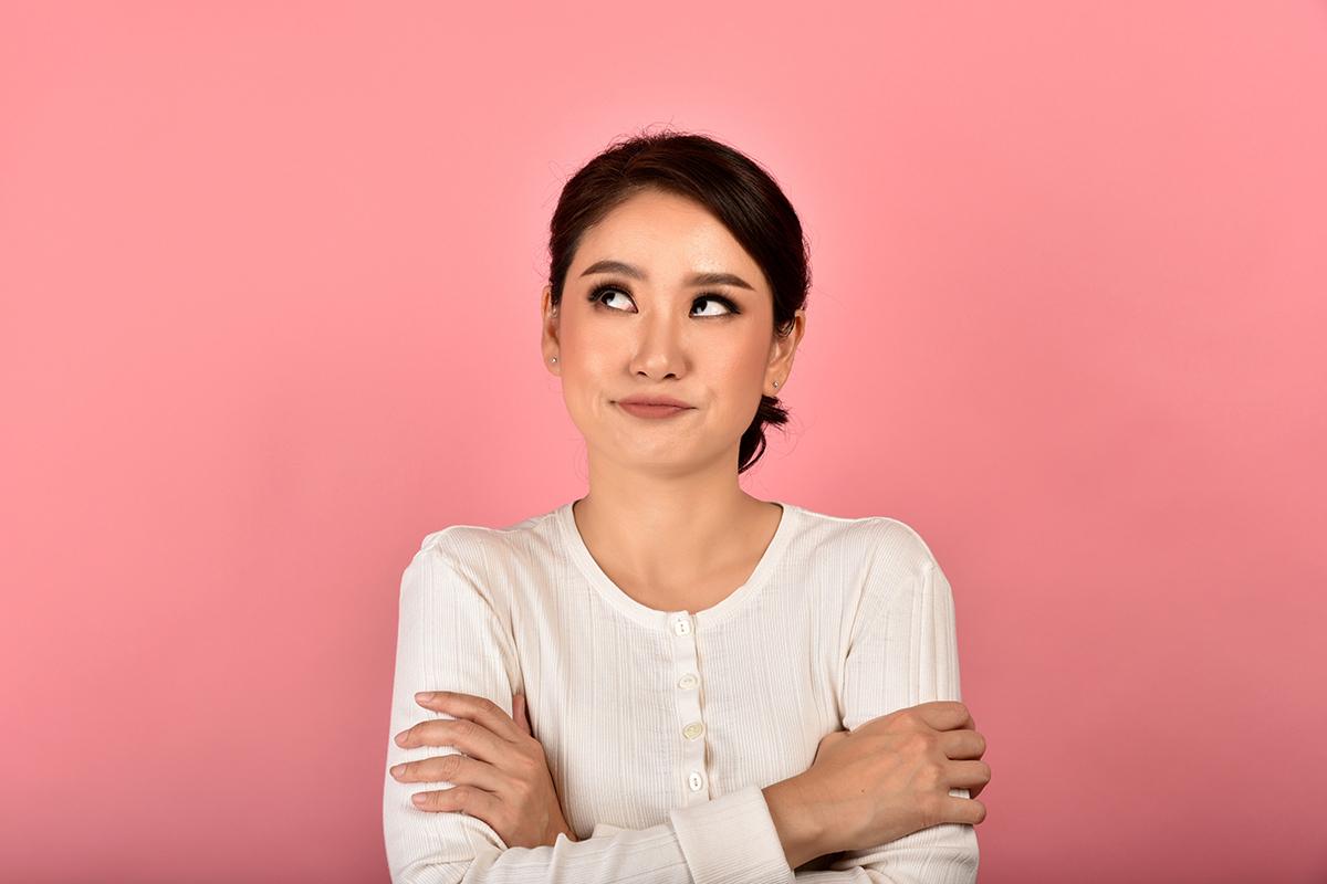 Vrouw met witte trui voor roze muur die niet geamuseerd, verveeld naar boven kijkt.