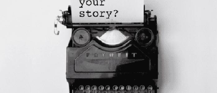 Oude typemachine met wit blad waarop 'what's your story' geschreven staat, 1 van de 3 essentiële bouwstenen in PowerPoint.
