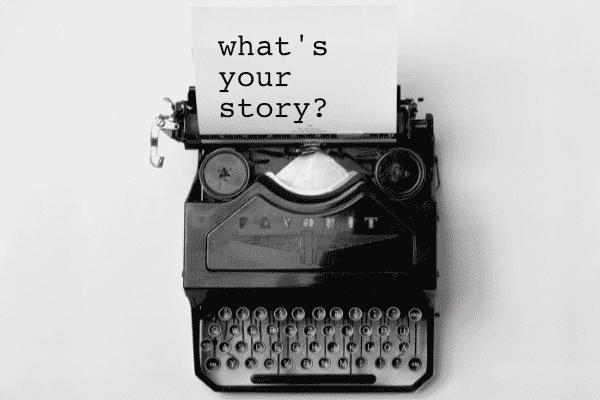 oude zwarte typmachine met wit blad waarop staat what's your story