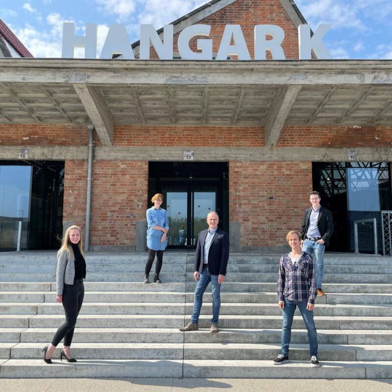 team Xiwa als stevige start-up, 5 personen staan op trappen van gebouw Hangar K in Kortrijk